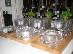 A sophisticated set with a bamboo three base with two tealights and a small pot in glass